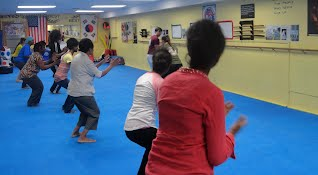 Dropping into base for balance at Women's self-defense class workshop at Bartman MMA and Self-Defense